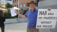 Paul Herman protesting outside the NAB Bank branch in Southport